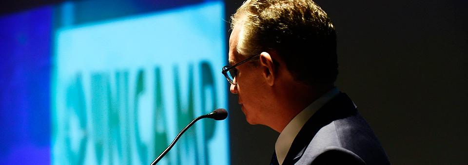 De perfil ao centro da foto o Professor Marcelo Knobel em discurso próximo ao microfone, ao fundo imagem do logo e o nome da Unicamp projetada na tela , cor de fonte preta e fundo branco