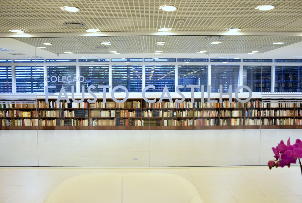 """foto mostra em primeiro plano uma parede de vidro com o letreiro """"coleção fausto castilho"""" e estantes de livros atrás"""