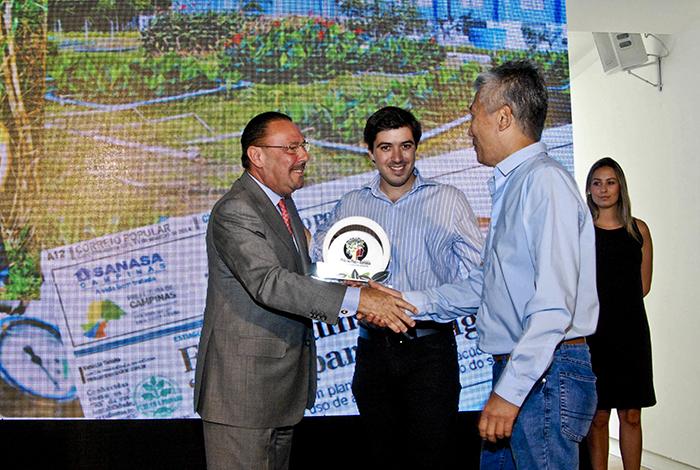 O pesquisador Eduardo e o docente Edson recebem o prêmio do presidente da RAC, Silvino de Godoy