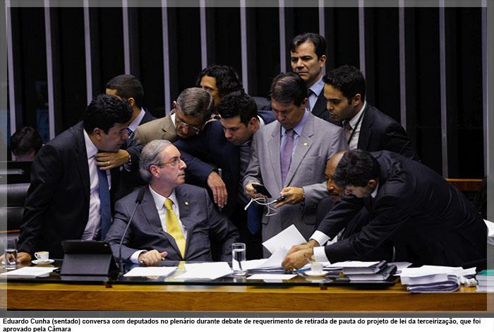Eduardo Cunha (sentado) conversa com deputados no plenário durante debate de requerimento de retirada de pauta do projeto de lei da terceirização, que foi aprovado pela Câmara