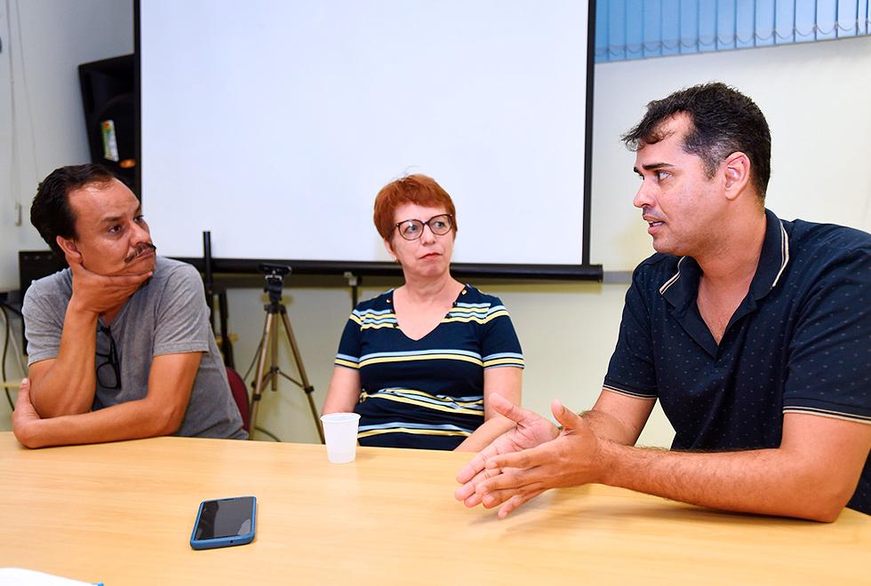 Foto mostra, da esquerda para a direita, Lauro Baldini, Marta Ferreira e Marcos Barbai. Eles estão reunidos em uma mesa conversando