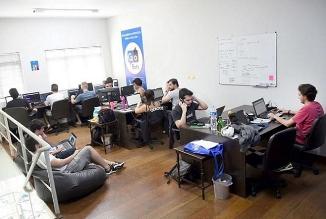 foto mostra o escritório da empresa gobots com funcionários sentados em escrivaninhas trabalhando em laptops e outros sentados em pufes. O ambiente é descontraído