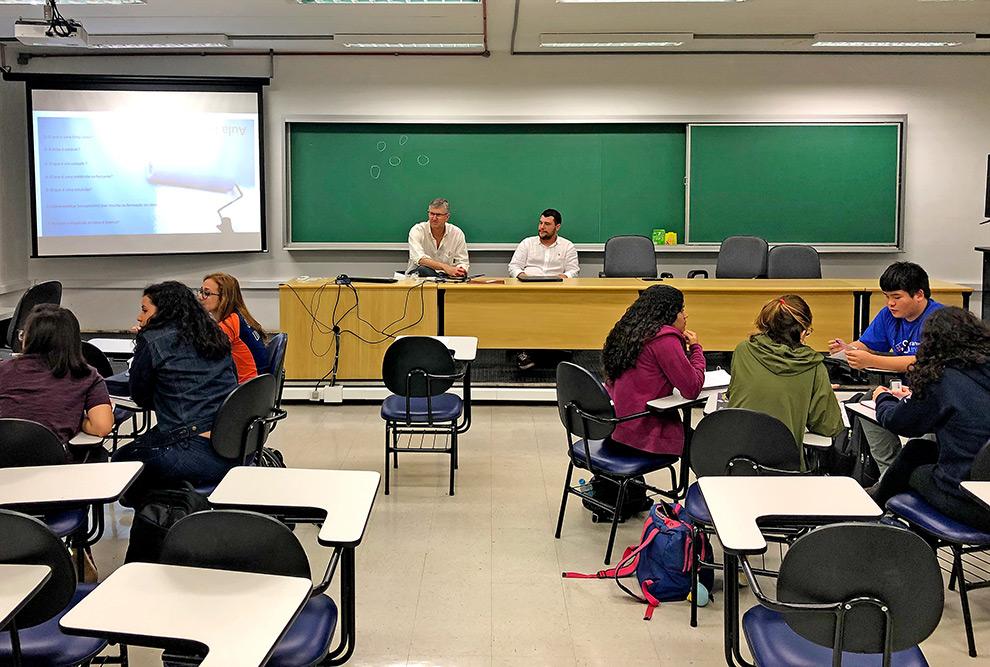 audiodescrição: fotografia colorida de sala de aula. na frente estão o professor edvaldo e o químico diego, ministrando aula. de costas, alguns alunos sentados nas carteiras de sala.