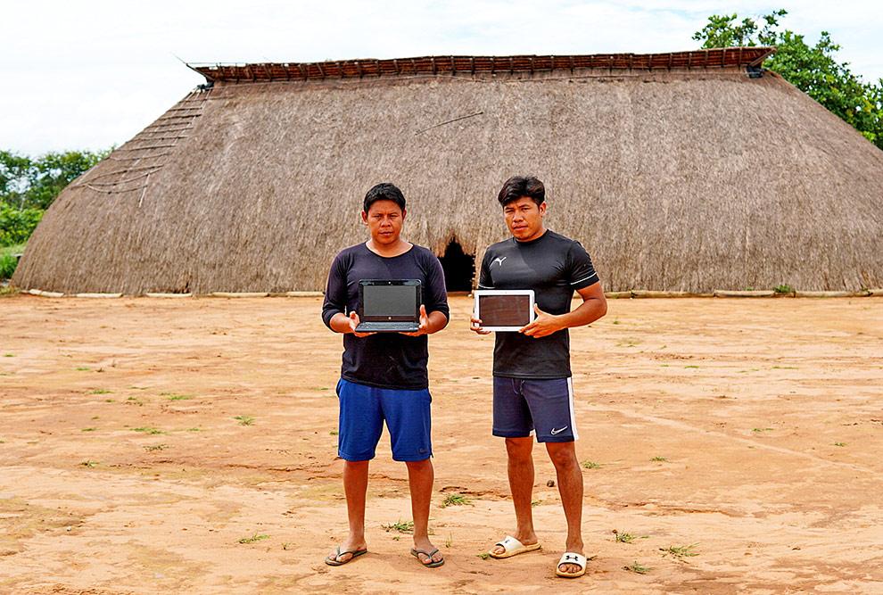 audiodescrição: fotografia colorida mostra dois estudantes indígenas, em frente a uma oca, segurando um computador e um tablet; eles estão posando para a foto