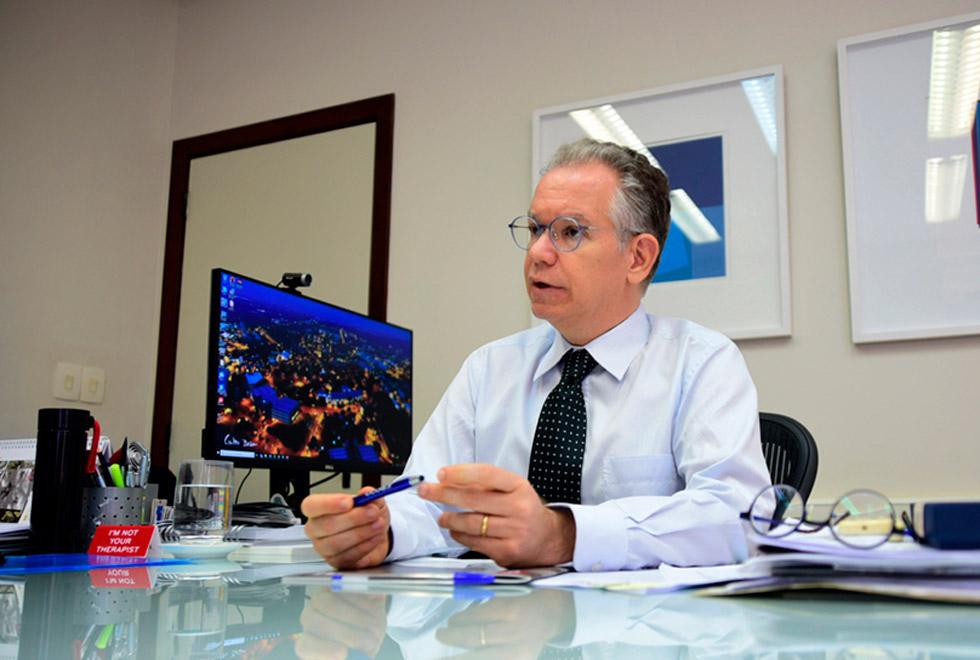 foto mostra o reitor marcelo knobel sentado à mesa de escritório