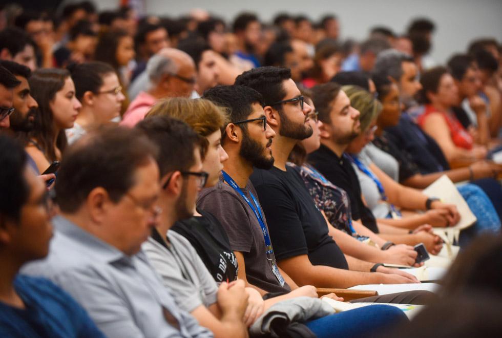 audiodescrição: fotografia colorida foca na plateia que assiste à palestra no centro de convenções