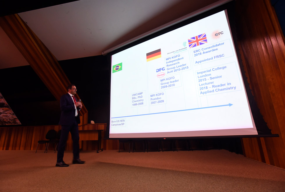 audiodescrição: fotografia colorida mostra professor roberto rinaldi em cima de palco enquanto ministra aula magna. há um slide projetado mostrando a trajetória acadêmica dele