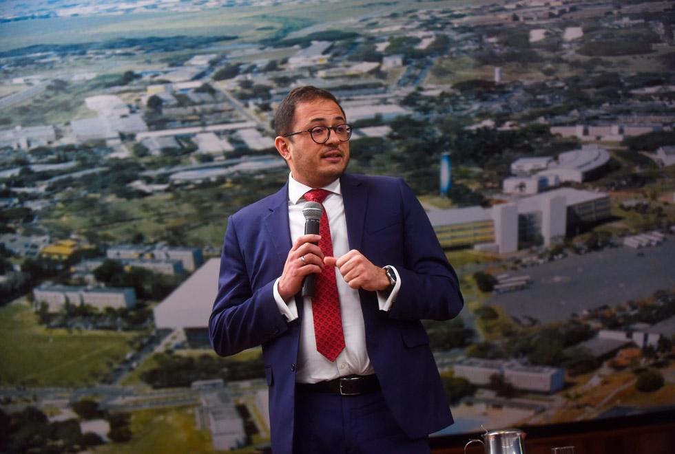 audiodescrição: fotografia colorida mostra professor roberto rinaldi ministrando palestra. ao fundo, há uma grande fotografia do campus da unicamp