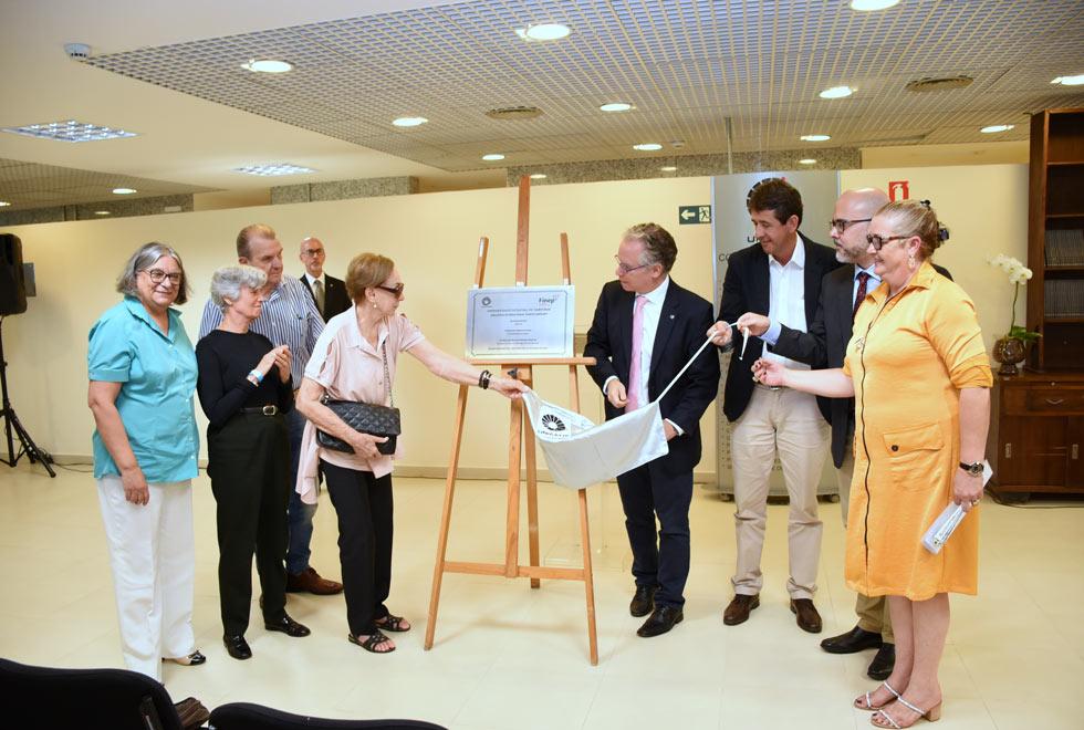 foto mostra dirigentes da universidade e convidados puxando o pano que cobria a placa de inauguração da biblioteca
