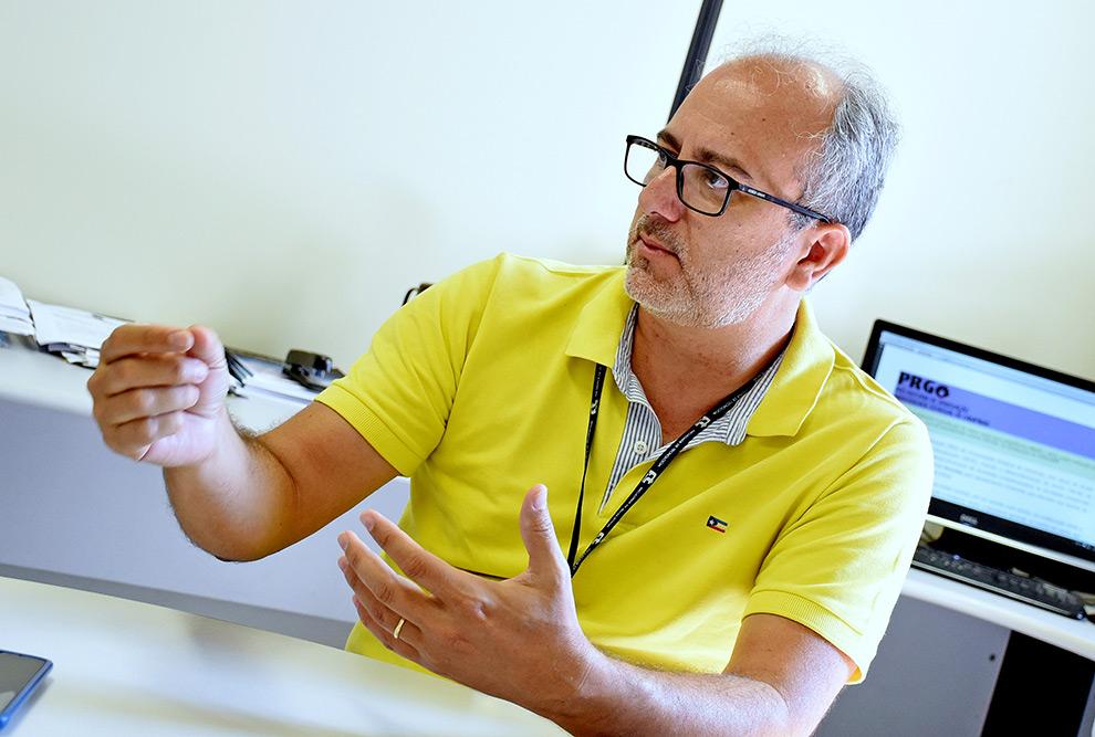 foto mostra professor marco antonio sentado em uma mesa gesticulando. ele veste camisa polo amarela