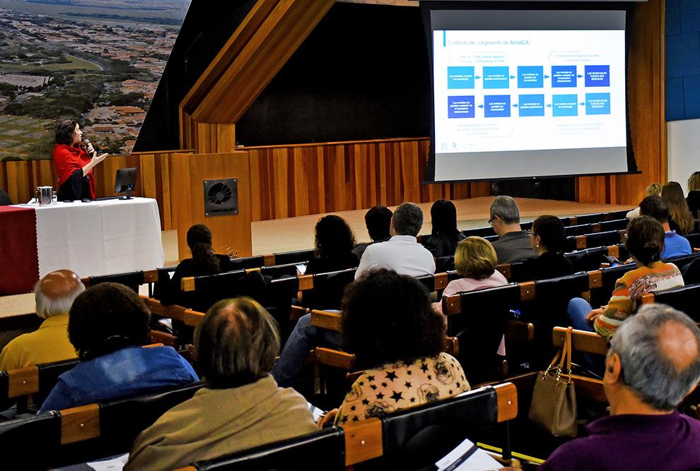 Palestrante está a frente do publico no auditório e ocupa a parte esquerda do quadro. à direita está o telão iluminado com um slide da palestra