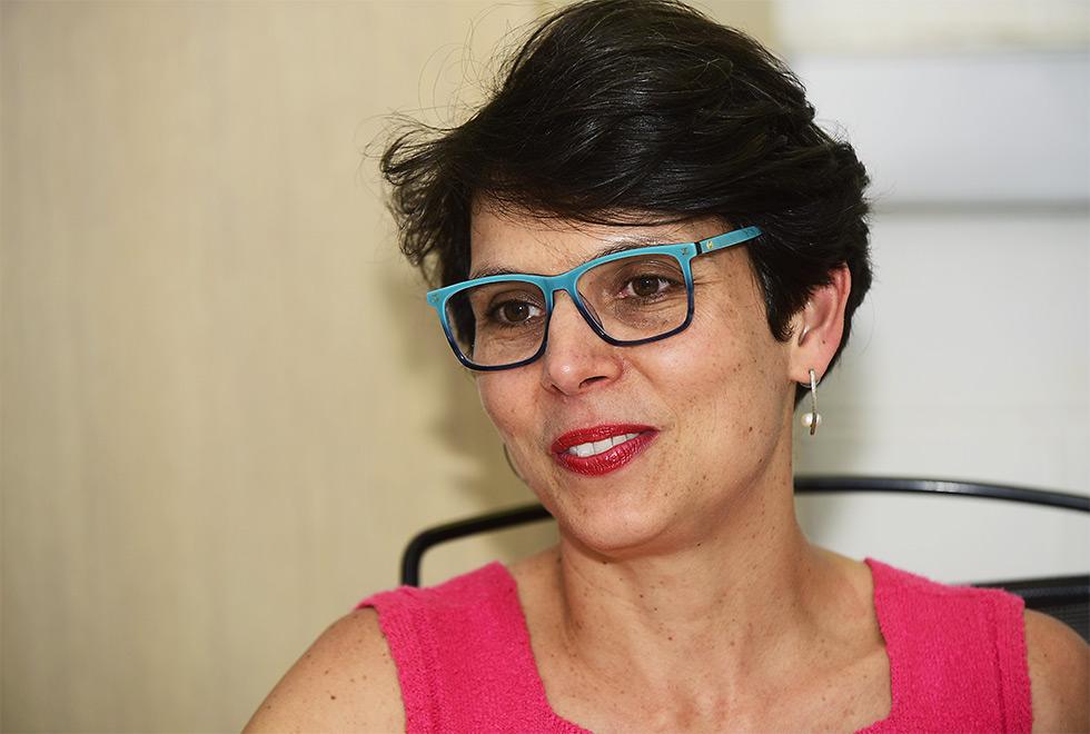 Helena Altmann durante a entrevista. Ela está de óculos de armação azul e quadrada e veste uma blusa sem mangas na cor rosa. Cabelos curtos.