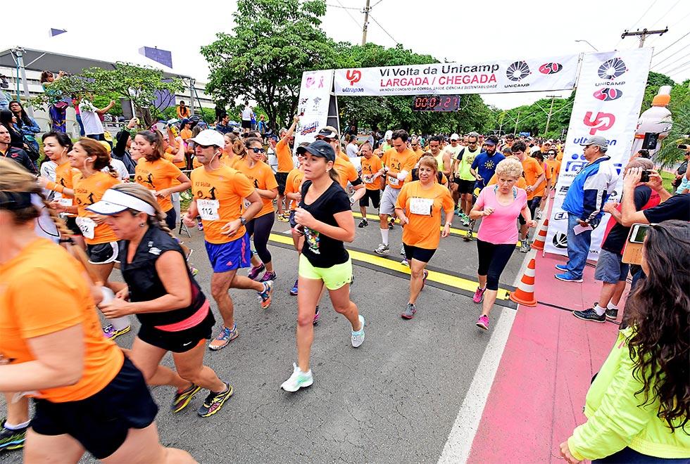 Vários corredores largam na corrida da Unicamp. Em evidência estão as mulheres. A maioria veste camisetas do evento na cor laranja. Há uma grande faixa onde está escrito Largada e Chegada