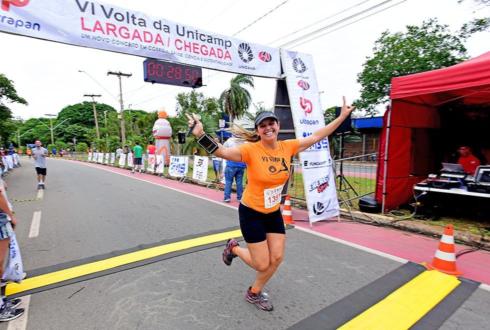 Mulher demonstra alegria ao cruzar a linha de chegada da corrida da Unicamp. Ela sorri e estende os braços. Veste a camiseta laranja do ecvento. Está de rabo de cavalo. Tem os cabelos compridos e loiros.