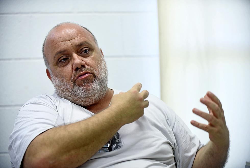 Professor Omar gesticula durante a entrevista. Ele é calvo e tem barba branca, está de camiseta clara e sobe os braços na altura do peito