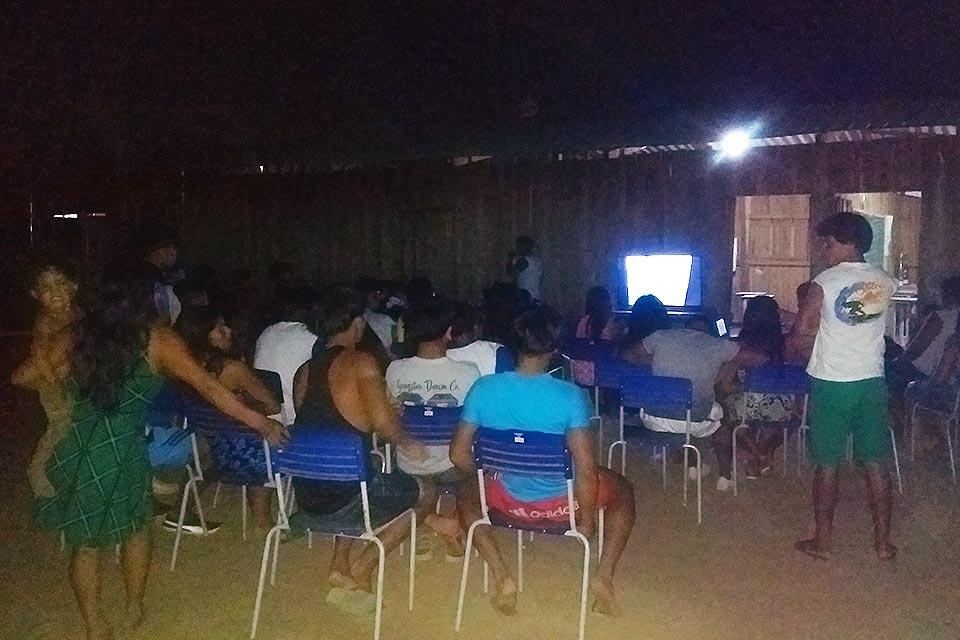 Foto: Divulgação - Comunidade indígena do Parque do Xingu sentada assistindo à filmes da própria aldeia