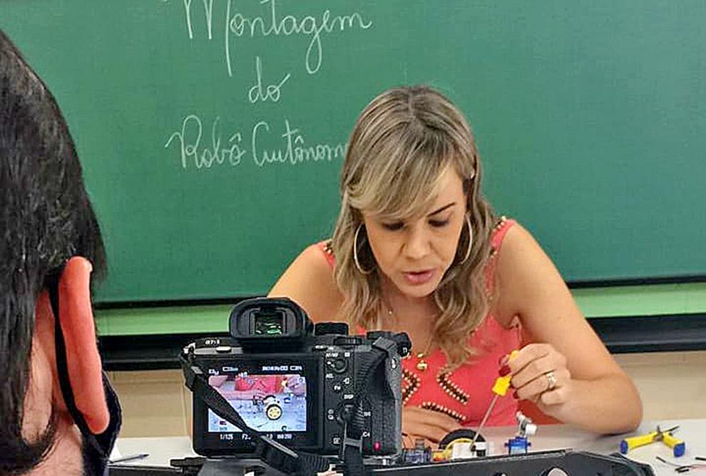 foto mostra uma câmera em primeiro plano filmando mariana matulovic demonstrando uma aplicação de robótica