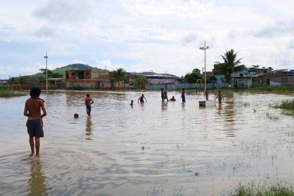 audiodescrição: fotografia colorida mostra área inundada. e crianças estão no meio da água