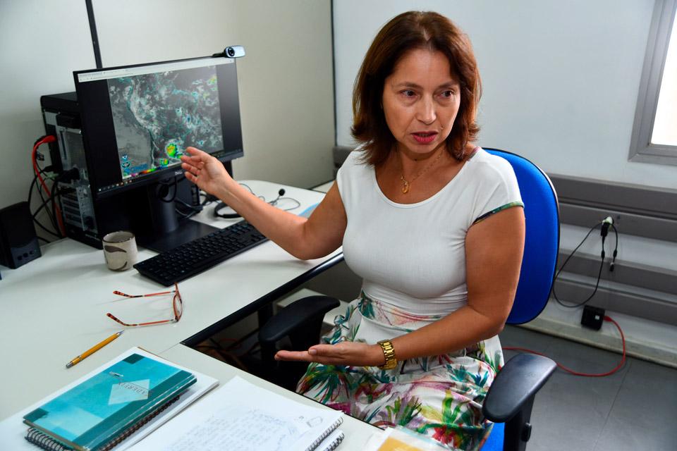 audiodescrição: fotografia colotida mostra professora Ana Ávila, do Cepagri, está sentada em mesa de escritório e no fundo, há uma imagem do mapa do Brasil mostrando o clima da região
