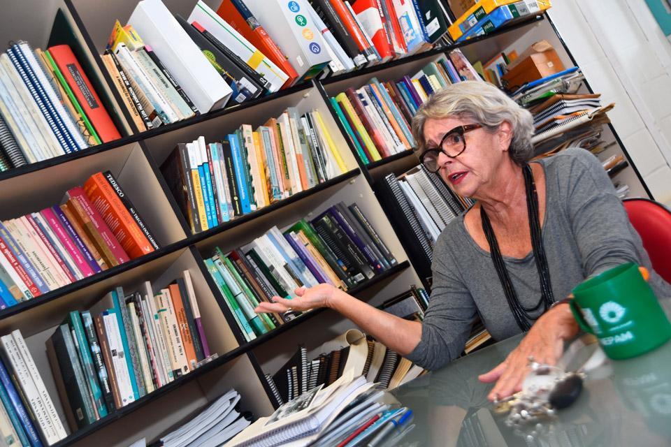 audiodescrição: professora Lúcia da Costa Ferreira, durante entrevista, está gesticulando com uma das mãos levantada. ela está sentada ao redor de uma mesa. ao fundo, há prateleiras com diversos livres