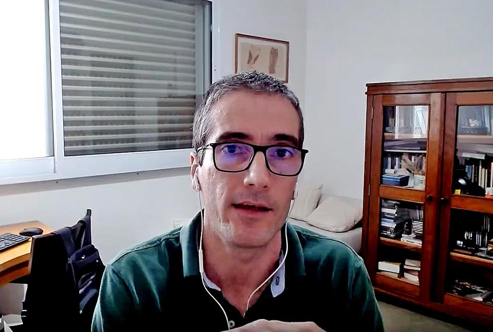 audiodescrição: fotografia colorida do professor alexandre gori, durante entrevista concedida online; ao seu lado há um armário com livros