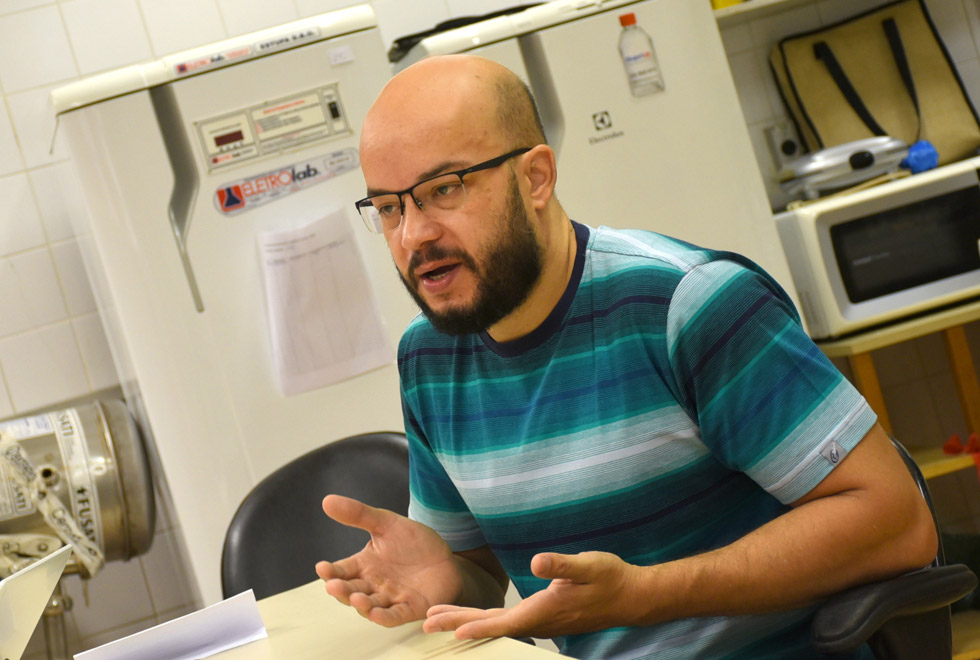 audiodescrição: fotografia colorida mostra homem de óculos gesticulando. ele usa óculos, camiseta azul listrada. ele está em um laboratório e ao fundo há geladeiras.