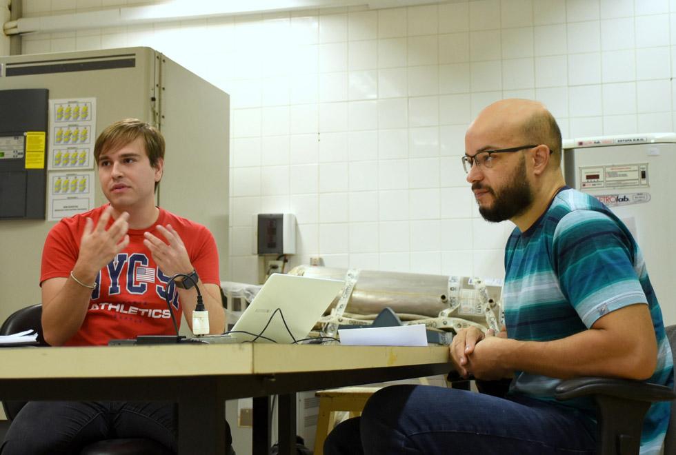 audiodescrição: fotografia colorida mostra dois homens, estudante e professor, em torno de uma mesa. o mais jovem, o estudante, gesticula enquanto fala. eles estão em um laboratório.