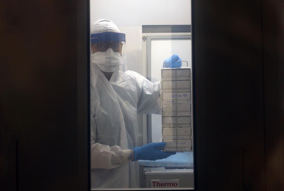 audiodescrição: fotografia colorida mostra pesquisador retirando o vírus Covid-19 do refrigerador