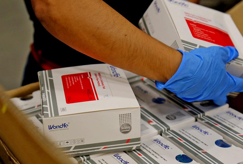 foto mostra mão com luvas segurando caixas de testes utilizados para detectar a Covid 19