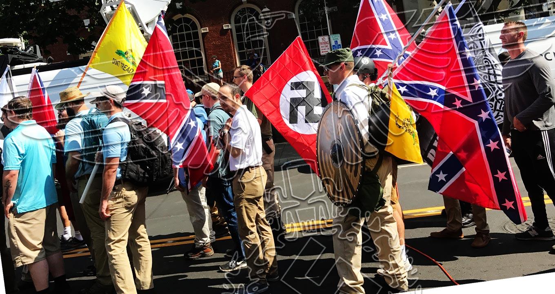 Audiodescrição: Em área externa, imagem em perspectiva, de costas e em plano médio, grupo de cerca de quinze homens caminha em passeata por rua, da direita para a esquerda, sendo que cinco deles carregam bandeiras de tecido em pequenos mastros apoiados nos ombros, deixando as bandeiras nas costas. São bandeiras diferentes, uma com símbolo nazista, uma amarela, e três dos Estados Confederados dos Estados Unidos, com fundo vermelho e uma cruz azul preenchida com treze estrelas brancas alinhadas. imagem 1 de 1