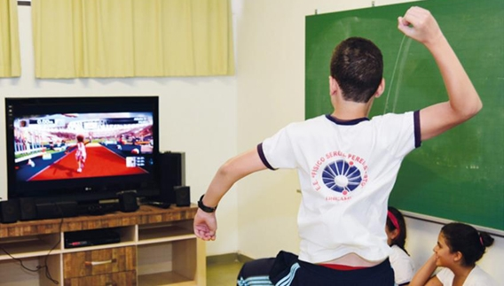 Estudantes do ensino fundamental durante atividade com videogame em aula de educação física