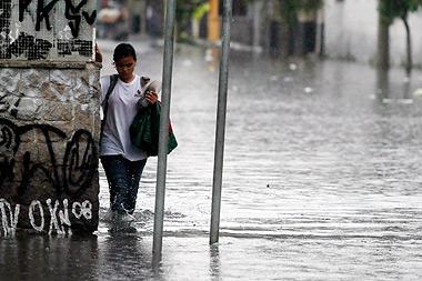 Pedestre em rua próxima à marginal Tietê passa por ponto de alagamento provocado por chuva que atingiu São Paulo na última semana de novembro: ocupação desordenada de leitos de rios agrava problema (Foto: Antoninho Perri)