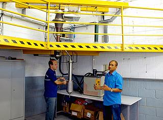 O pesquisador Walfrido Alonso Pippo (à dir.), pós-graduando sênior, ao lado de reator usado nas pesquisas do Grupo Combustíveis Alternativos (Fotos: Antoninho Perri)