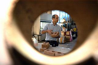 O professor Armando Lopes Moreno Junior e os tijolos feitos com mistura de solo e cimento: produto de excelente qualidade e mais barato do que o convencional (Foto: Antoninho Perri)